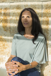 Portrait of mature woman sitting at shadow looking up - JUNF01573