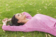 Mature woman wearing pink shirt relaxing on a meadow in summer - JUNF01585