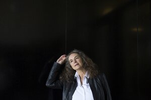 Portrait of mature woman wearing black leather jacket looking at distance - JUNF01609