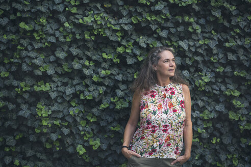 Portrait of relaxed mature woman standing in front of wall overgrown with ivy wearing top with floral design - JUNF01630