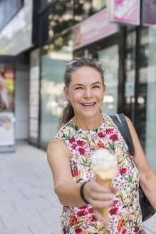 Portrait of smiling mature woman with ice cream cone in the city - JUNF01633
