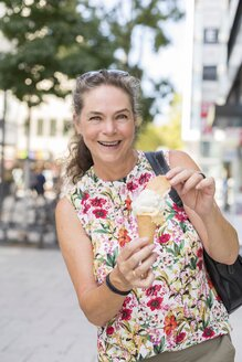 Portrait of smiling mature woman with ice cream cone in the city - JUNF01636