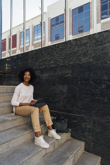 Young casual businesswoman using tablet, sitting on steps - BOYF01271
