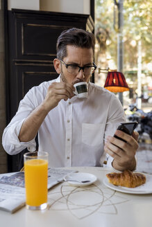 Businessman having breakfast in a cafe and checking cell phone - MAUF01955