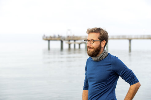 Germany, Rerik, bearded man in front of the sea looking at distance on hazy day - PUF01346