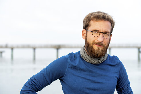 Germany, Rerik, portrait of bearded man in front of the sea wearing metal-rimmed spectacles - PUF01349