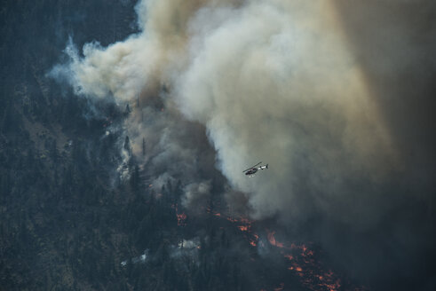 Seaplane flying over mountains during forest fire at Grand Teton National Park - CAVF60354