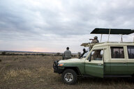 Male friends on off-road vehicle at Serengeti National Park during sunset - CAVF60411