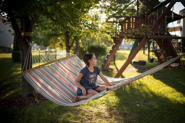Thoughtful girl looking away while sitting on hammock at playground - CAVF60429