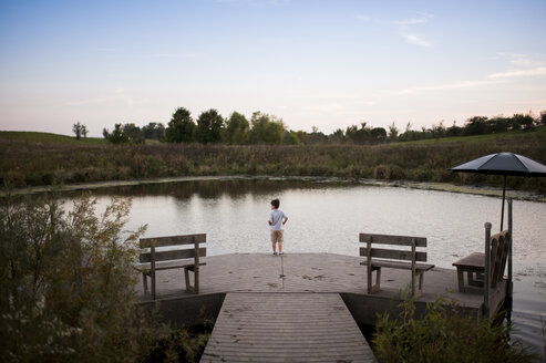 High angle view of boy standing on pier over lake at park - CAVF60432