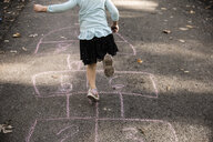 Low section of girl playing on hopscotch - CAVF60444