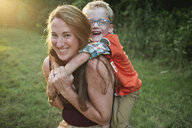 Portrait of happy mother piggybacking son while sitting on grassy field in forest - CAVF60459