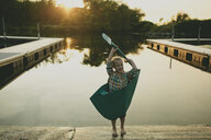 Happy boy wearing boat costume while standing by lake during sunset - CAVF60462