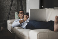 Happy young man lying on sofa at home using cell phone and laptop - ERRF00359