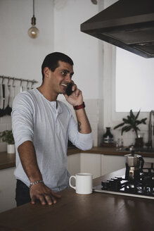 Smiling young man on cell phone in kitchen at home - ERRF00368