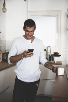 Smiling young man with cup of coffee using cell phone in kitchen at home - ERRF00371