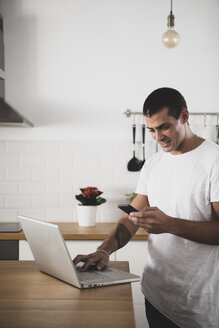 Smiling young man using laptop and cell phone in kitchen at home - ERRF00389