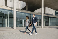 Two colleagues walking outside office building - JRFF02185
