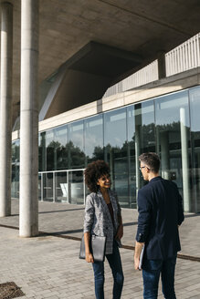 Two colleagues talking outside office building - JRFF02188
