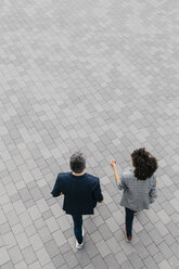 Top view of two colleagues walking on a square - JRFF02215