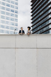 Two colleagues talking outside office building - JRFF02218