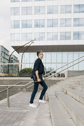 Businessman walking on stairs outside office building in the city - JRFF02224