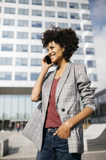 Smiling businesswoman on cell phone outside office building - JRFF02230