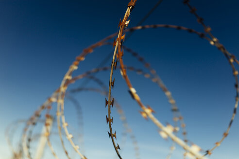 Part of barbed wire fence against blue sky - DASF00080