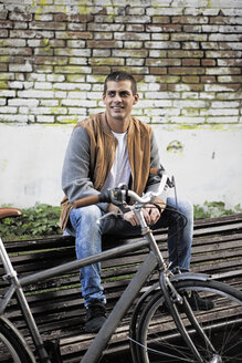 Young man sitting on a bench next to bicycle - ERRF00396