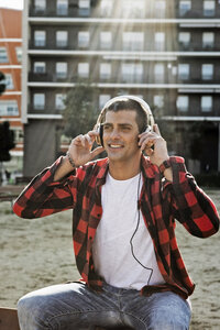 Smiling young man sitting outdoors in the city wearing headphones - ERRF00405