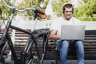 Young man sitting on a bench wearing headphones and using laptop next to bicycle - ERRF00411