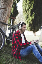 Young man sitting in a park wearing headphones and using laptop next to bicycle - ERRF00417