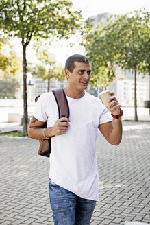 Smiling young man with takeaway coffee on the go - ERRF00420