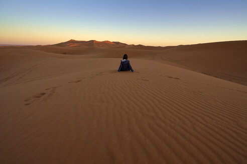 Morocco, back view of woman sitting on desert dune at twilight - EPF00506