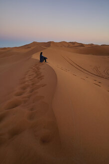 Morocco, woman sitting on desert dune at twilight - EPF00509