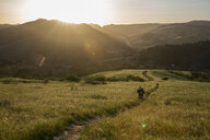 High angle view of man on trail amidst grassy field against mountains during sunset - CAVF60482