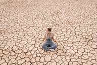 High angle view of woman sitting on barren landscape - CAVF60497