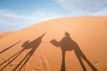 Shadow of friends riding camels on sand at Merzouga desert against sky - CAVF60503