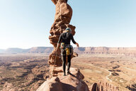 Rear view of female hiker walking on rock formation against clear sky during sunny day - CAVF60527