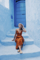 Woman looking up while sitting on steps by house - CAVF60587
