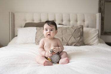 Full length of cute shirtless baby boy with stuffed toy sitting on bed at home - CAVF60614