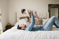 Playful father lifting son while lying by daughter on bed at home - CAVF60623