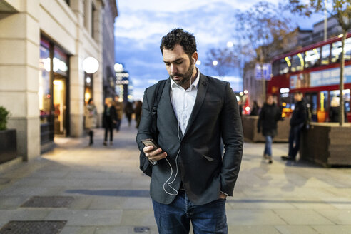 UK, London, businessman on the go checking his phone while commuting by night - WPEF01184