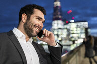 UK, London, portrait of smiling businessman talking on the phone while commuting by night - WPEF01187