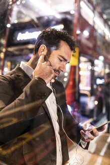 UK, London, businessman with cell phone and earbuds at the bus station by night - WPEF01193