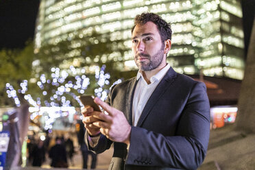 UK, London, businessman on the go holding cell phone while commuting by night - WPEF01199