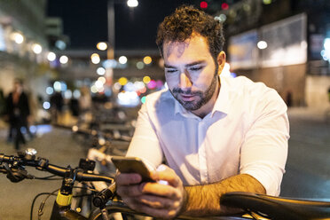 UK, London, smiling man looking at his phone by night - WPEF01202