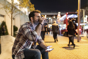 UK, London, man sitting on a bench by night drinking from mug - WPEF01205