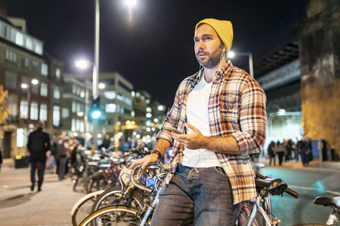 UK, London, man with bicycle and cell phone commuting at night in the city - WPEF01208