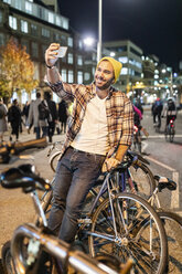 UK, London, man taking a selfie while commuting at night in the city - WPEF01211